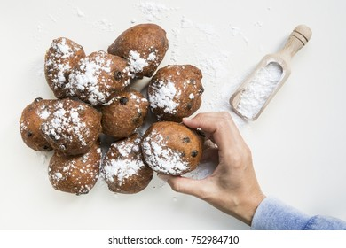 hand packing, traditional Dutch oliebollen, oil dumpling or fritter, with wooden spoon, for New Year's Eve