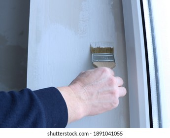 hand with a paint brush applies a layer of white paint to the surface of the side window slope close-up, redecoration of the room, manual renewal of staining, work with water-based white paint