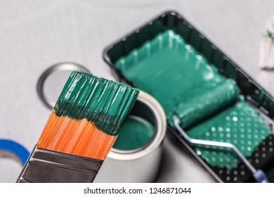 Hand with paintbrush and green paint and other tools in soft focus in back