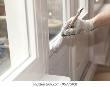 Hand with paintbrush painting a door white