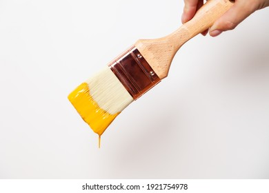 Hand with paintbrush with yellow paint drips off the brush