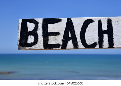 hand painted beach sign and sea background