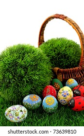 Hand painted beautiful  colorful  easter eggs in wicker basket on fresh green grass