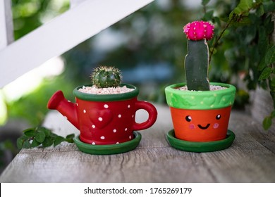 Hand Painted Cactus Pots at Home. Two Bright and Smiley Pots Outside on Wood Steps.