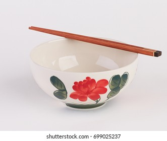 Hand painted ceramic soup bowl with wooden chopsticks isolated on white background