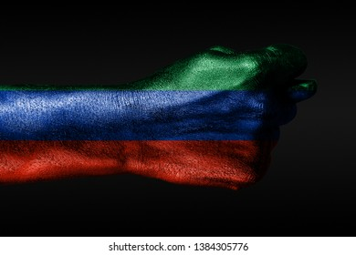 A hand with a painted Dagestan flag shows a fig, a sign of aggression, disagreement, a dispute on a dark background. Horizontal frame