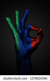 A hand with the painted flag of Dagestan shows an OK sign on a dark background. Vertical frame