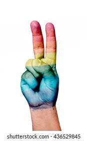 Hand painted with the flag of gay pride making peace gesture with fingers on white background