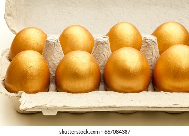 hand painted gold eggs in an egg carton