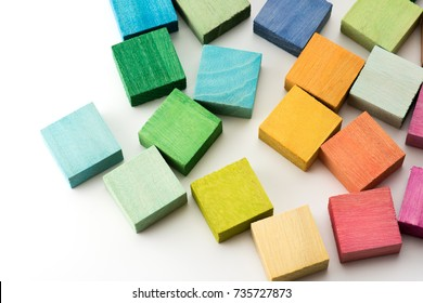 Hand painted multi colored wooden blocks on white table.  Background or cover for something creative or diverse.
