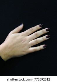 hand with painted nails in dark purple on a black background
