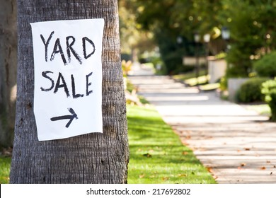 Hand painted paper yard sale sign with direction arrow stapled to a palm tree.