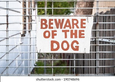 Hand painted red and cream sign wired onto a wire fence by the side of a house stating: BEWARE OF THE DOG
