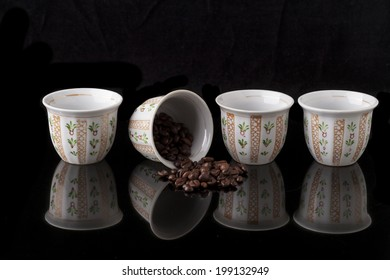 Hand painted traditional arabic coffee cups on black background and coffee beans with reflection