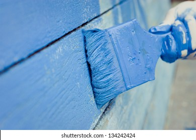 hand painting blue wooden wall