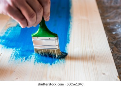 Hand with painting brush, painting wooden panel in blue