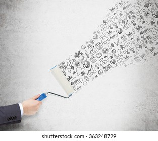 Hand painting a concrete wall with a roller, icons of coins, dollars, bulbs, puzzles, bar charts, graphs, notes, arrows appearing on the wall. Concept of giving new ideas
