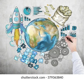 A hand painting the Earth in colour surrounded by graphs, rocket, cogwheels, puzzle. Front view. Concrete background. Concept of international business. Elements of this image furnished by NASA.