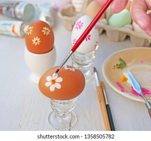 Hand painting Easter eggs with paintbrush. Easy design, fun craft for children.