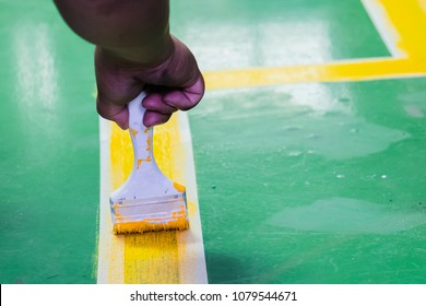 hand painting yellow action line marking, safety lines painting in green floor in industry factory.