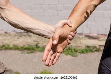 A man's hand with pale skin holds a tanned man's hand by the wrist. Close up. Martial arts instructors demonstrate self-defense techniques of Krav Maga
