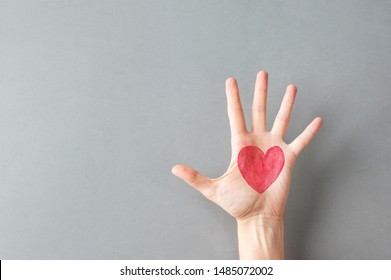 Hand palm of young Caucasian woman girl with painted on red heart on gray wall background. Charity love donation Valentine health concept. Creative social poster banner with copy space