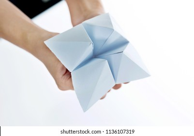 Hand in paper fortune teller isolated on white background.