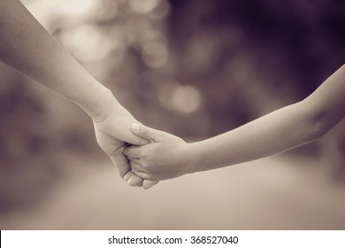 hand of parent and child on the background blurred nature.Mother holding hands baby style sepia tones.
