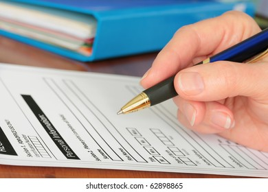 Hand with Pen Completing Personal Information