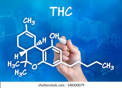 hand with pen drawing the chemical formula of thc