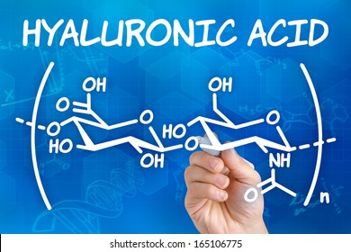 Hand with pen drawing the chemical formula of hyaluronic acid