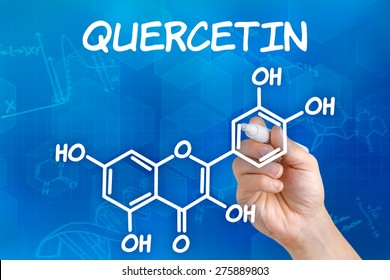 Hand with pen drawing the chemical formula of Quercetin
