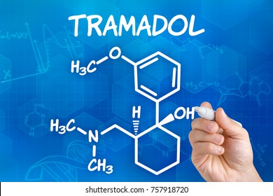 Hand with pen drawing the chemical formula of Tramadol