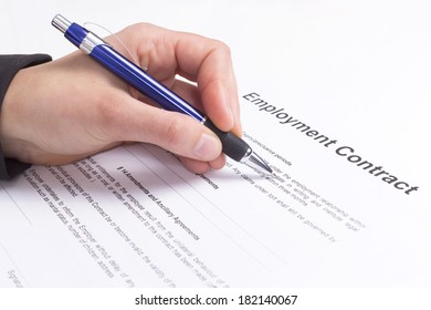 Hand with pen and employment contract