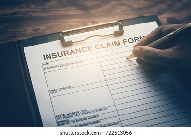Hand with pen on application form for registering claim health insurance