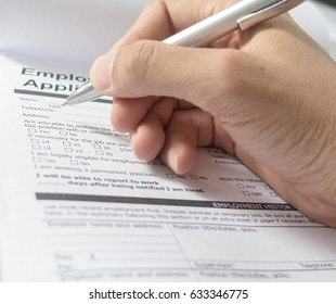 Hand with pen over application form, Filling name in personal de