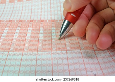 hand and pen playing luck game checking numbers