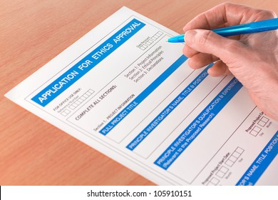 Hand with Pen Writing on Ethics Approval Application Form for a Research Project