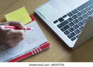 Hand pen writing schedule on calendar business work plan with laptop