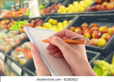 Hand with a pen writing a shopping list in supermarket  by fruit - focus on foreground
