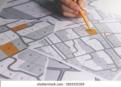 hand with pencil on cadastral map - choose and buy a building plot for house construction - Shutterstock ID 1831925359