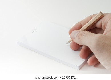Hand with pencil writing on a blank paper
