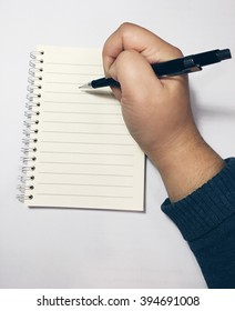 Hand with pencil writing in open book