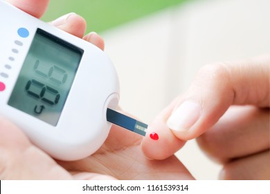 hand of people check diabetes and high blood glucose monitor with digital pressure gauge. Healthcare and Medical concept