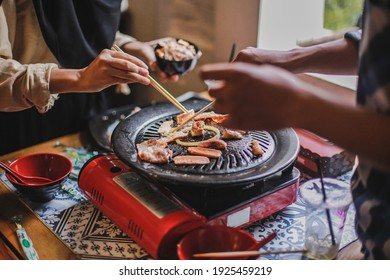 Hand of people cooking barbecue meat with chopsticks. Concept of summer party with families and friends