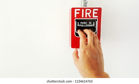 Hand of people pressing fire alarms to notify the fire in the factory.