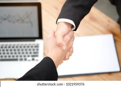 Hand of people shake hand make a deal on a business together in his office.working assemble corporate meeting show symbol join forces teamwork quality and effective personnel Concept organizational