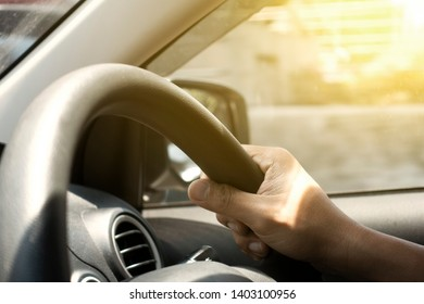 Hand of people touching car's steering when driving.