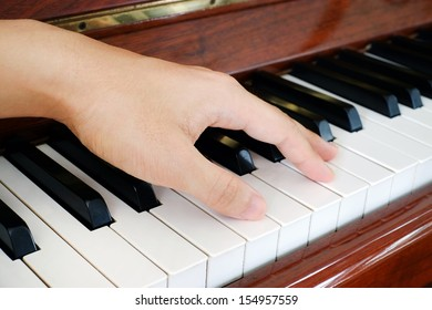 A hand of a performer on the piano