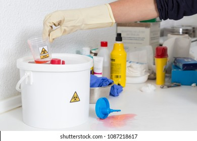 hand of a person cleaning with the proper gloves, a waste bottle labeled as biological risk in what looks like a nursing consultation shelf